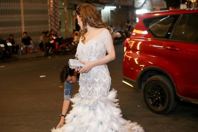 Diện bộ váy lông vũ dài quét đất, Lâm Khánh Chi phải rất cẩn thận khi di chuyển. Ông xã Trần Phi Hùng ân cần chỉnh váy cho vợ trước khi cô chụp ảnh cùng bạn bè.