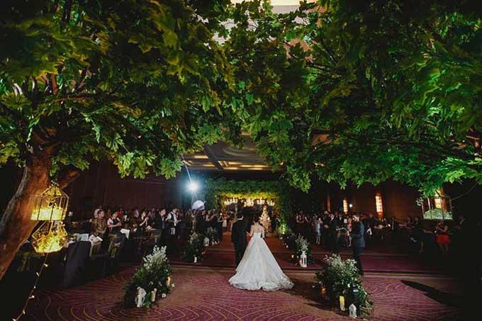 Cô dâu, chú rể bước qua con đường giữa hai hàng cây cổ thụ để tiến đến sân khấu trung tâm.