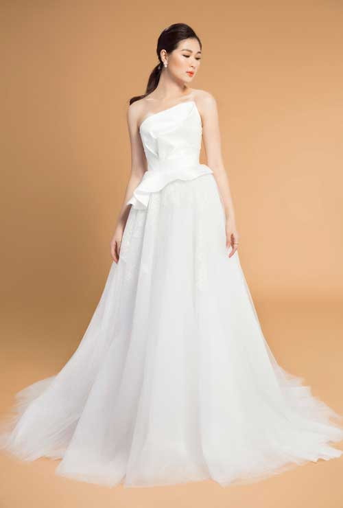 Váy cưới chữ A: Không quá khó để lý giải vì sao kiểu dáng váy này luôn nằm trong danh sách best seller của các nhà mốt bởi tính ứng dụng cao. Với thiết kế ôm sát phần thân áo,xòe nhẹ từ eo trở xuống, váy cưới chữ A phù hợp với mọi cô dâu, đặc biệt là các cô dâu mũm mĩm vì nó có thể che được khuyến điểm vòng 2, vòng 3 và kéo dài thân một cách tự nhiên.