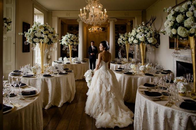 Phòng tiệc cưới bố trí bàn tròn và được trang trí bằng hai tông vàng đồng, trắng cổ điển.