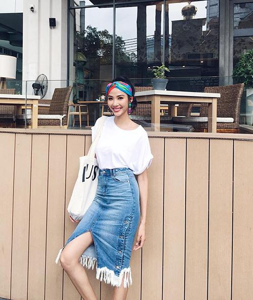 Hoàng Thuỳ diện style mùa hè đơn giản nhưng không kém phần sành điệu với chân váy jeans tua rua với áo phông trắng. kết hợp với khăn turban sặc sỡ.