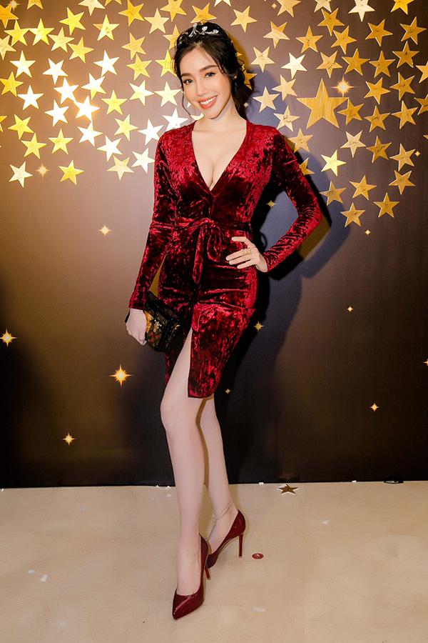 Elly chọn bộ váy nhung đỏ đô xẻ ngực sâu và xẻ phần thân để phô vẻ gợi cảm.