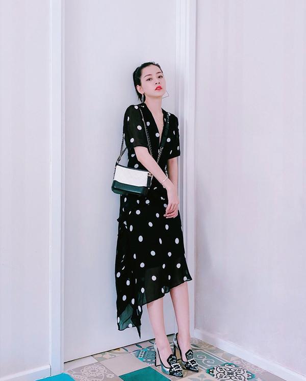 Đầm mang hơi hướng cổ điển với hoạ tiết chấm bi đen trắng được Chi Pu phối hợp nhịp nhàng cùng túi hiệu Chanel và giày mũi nhọn trang trí hoạ tiết bắt mắt.