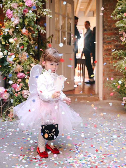 Em bé Lilix - cháu của cô dâu, đáng yêu trong chiếc váy bồng với cánh bướm trên vai và chiếc túi hình con mèo.
