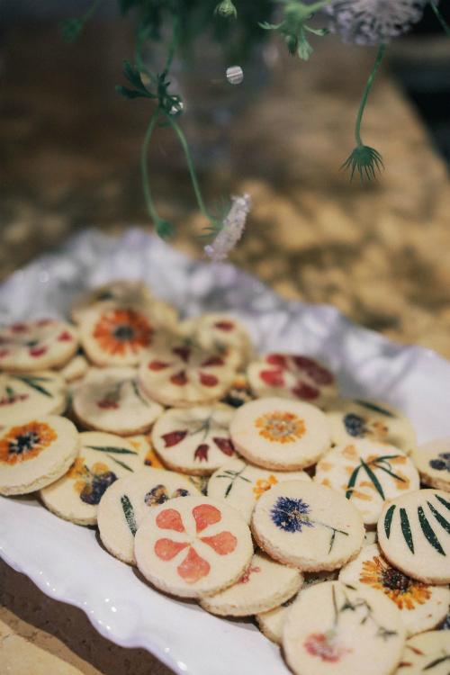 Không gian tiệc cưới thêm phần ấn tượng với những bình hoa nhí và bánh quy hoa tươi.