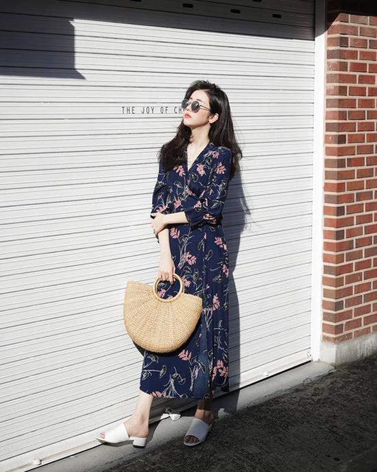 Váy hoa vạt quấn kiểu dáng cổ điển được kết hợp cùng túi cói nửa vầng trăng và sandal kiểu dáng đơn giản mang lại sự thông thoáng cho đôi chân.
