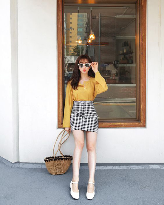 Kết hợp cùng kiểu váy ca rô trẻ trung, áo lụa vàng mù tạt là mẫu túi nan trang trí bông len xinh xắn, tô điểm cho miệng túi.