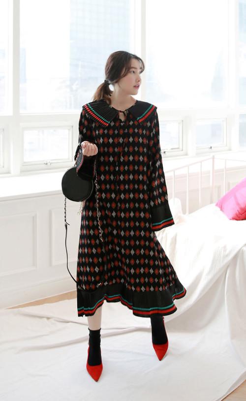 Váy suông hoa tiết ấn tượng đi cùng túi trống tròn xinh, giày mũi nhọn màu đỏ nổi bật.