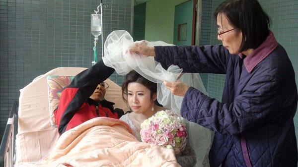 Ông Hou dành chút sức lực cuối để phủ khăn choàng đầu cho con gái.