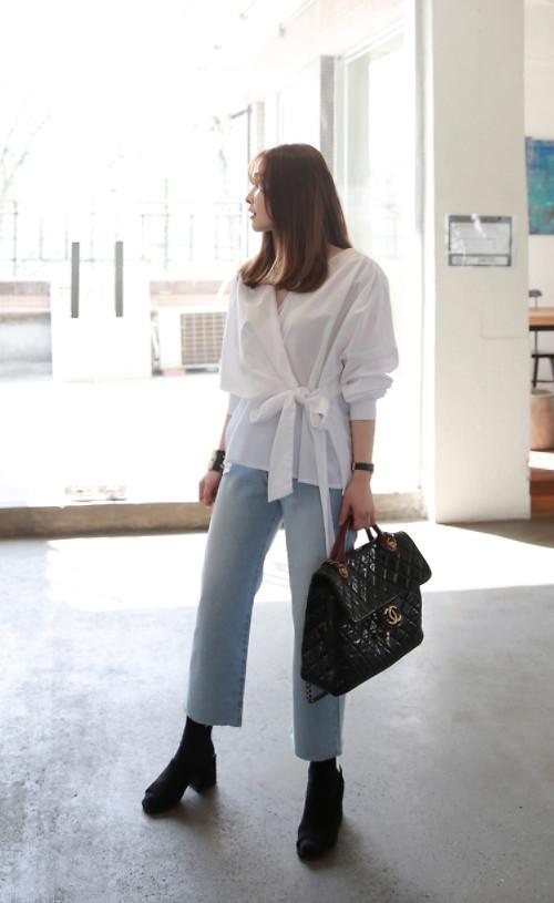 Đối với những cô nàng yêu phong cách đơn giản thì có thể chọn áo vạt quấn trên sắc trắng đi cùng quần jean ống suông.