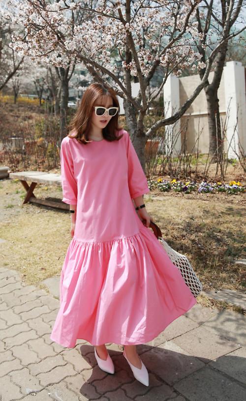Váy hạ eo với sắc hồng ngọt ngào sẽ giúp bạn gái tôn nét nữ tính. Phối cùng mẫu váy phom rộng là kiểu túi lưới hot trend đi cùng mắt kính và giày đế thấp tiệp sắc trắng.