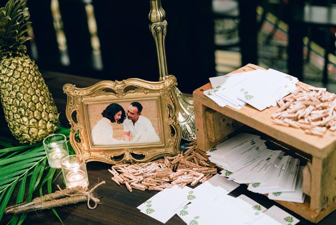 Ảnh cưới của cô dâu chú rể được lồng trong khung màu vàng đồng, xung quanh có các đồ vật trang trí tiệp màu như trái dứa sơn nhũ vàng, giá nến...
