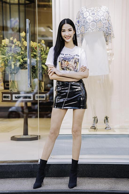 Hoàng Thuỳ khoe chân dài sexy với thiết kế váy da bóng phối cùng áo thun hot trend, bốt cổ thấp.