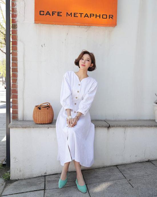 Set đồ hoàn hảo để mang lại cảm giác nhẹ nhõm khi xuống phố với váy suông cài nút tông trắng, làn tre xách tay, giầy bệt xanh pastel dịu mắt.