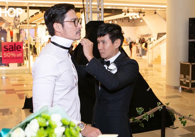 Lý Hải giúp Huy Khánh chỉnh sửa trang phục trước khi sự kiện bắt đầu.