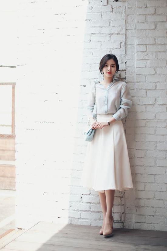 Chân váy midi mang đường nét của phong cách cổ điển là trang phục rất quen thuộc nhưng không gây nhàm chán. Bởi nó có thể mặc ở nhiều mùa và dễ dàng phối hợp cùng nhiều kiểu áo khác nhau để mang lại nét thanh lịch cho bạn gái văn phòng.