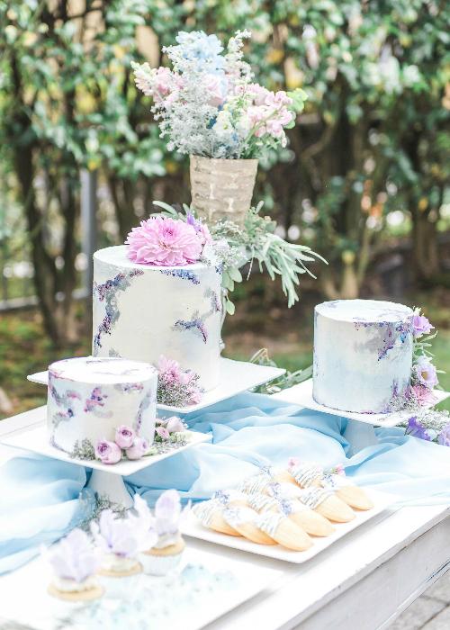 Bánh cưới đính hoa tươi và phủ kem phong cách màu nước đồng điệu với cả không gian tiệc.
