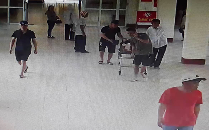Nhóm người đàn ông đưa thai phụ bị tai nạn giao thông vào làm thủ tục nhập viện. Ảnh: Trích xuất camera
