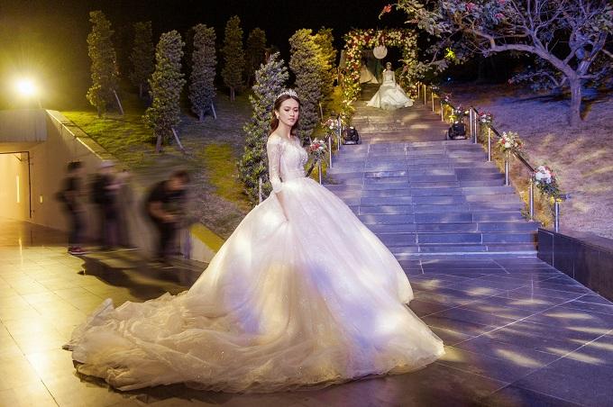 Một trong những chiếc váy đặc sắc nhất trong BST  Dream of Eden là thiết kế trể vai dài tay nhẹ nhàng nhưng lại không kém phần quý phái.  Điểm nổi bật của chiếc váy cưới này  là sự kết hợp hài hòa giữa chất liệu  ren pháp cao cấp và những hạt pha lê lấp lánh, tạo nên vẻ đẹp tinh tế và hoàn hảo nhất, giúp nàng dâu có thể tự tin tỏa sáng trong ngày trọng đại của mình.
