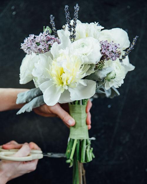 Khi đã ưng ý với tạo hình của bó hoa cưới, bạn dùng băng dính để cố định phần thân. Cố gắng quấn thật chặt tay và dùng kéo cắt sao cho phần cành hoa lộ ra bên dưới có độ dài bằng nhau.