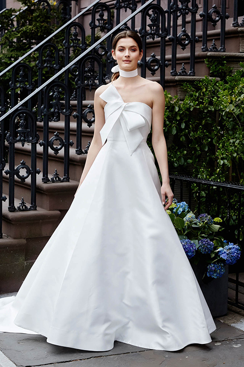 Váy cưới với những chiếc nơ quá khổ:Những chiếc nút thắt hình nơ đem đến cái nhìn lãng mạn, cổ điển cho cô dâu. Trong những mẫu váy này, nơ được may trước ngực và sau lưng nhằm tạo điểm nhấn độc đáo.