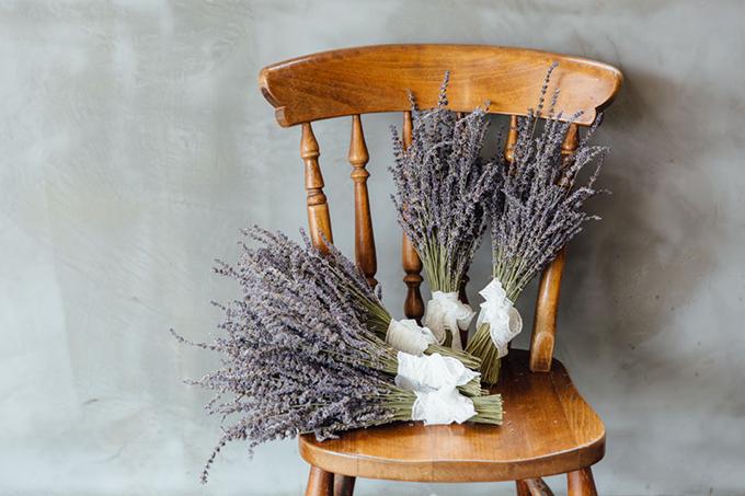 Ngoài ra, các cô dâu có thể tận dụng hoa oải hương khô để tạo thành bó hoa nhỏ đặt ở ngoài bàn tiếp tân. Đầu tiên, bạn sắp xếp hoa oải hương thành bó nhỏ, sau đó quấn chúng lại bằng dây ruy băng ren trắng. Không chỉ đẹp, hoa oải hương tím còn có ý nghĩa đem lại may mắn và tượng trưng cho sự thuỷ chung.