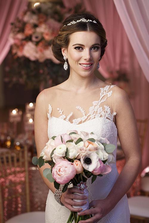 Hoa cưới cầm tay của cô dâu được kết từ những bông hoa có sắc màu hồng, cam và trắng.