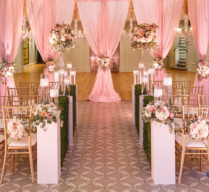 Hôn lễ hiện đại ngày càng đa dạng về màu sắc và cách bài trí. Sự kết hợp giữa màu hồng phấn và màu trắng tinh khôi sẽ làm tăng thêm sự hài hoà cho đám cưới lãng mạn mang màu sắc cổ tích.Sảnh tiệc được trang trí với màu hồng bắt mắt, tạo ấn tượng cho khách mời. Để làm nổi bật thêm gam màu này, cô dâu chú rể đã bổ sung các tông màu khác như màu vàng từ những chiếc ghế, màu trắng của hoa, màu xanh của thảm lá và sử dụng đèn chiếu màu hồng.