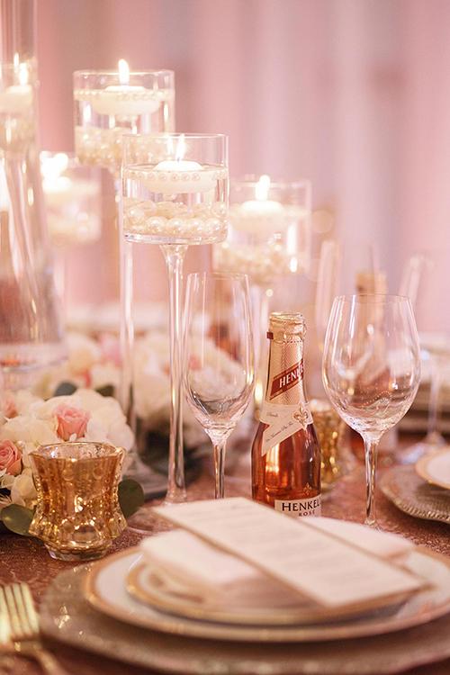 Bàn tiệc hiện đại và sang trọng nhờ những bông hoa có sắc hồng, những chiếc tách vàng lịch lãm, cây nến được thắp sáng trong ly ngọc trai.