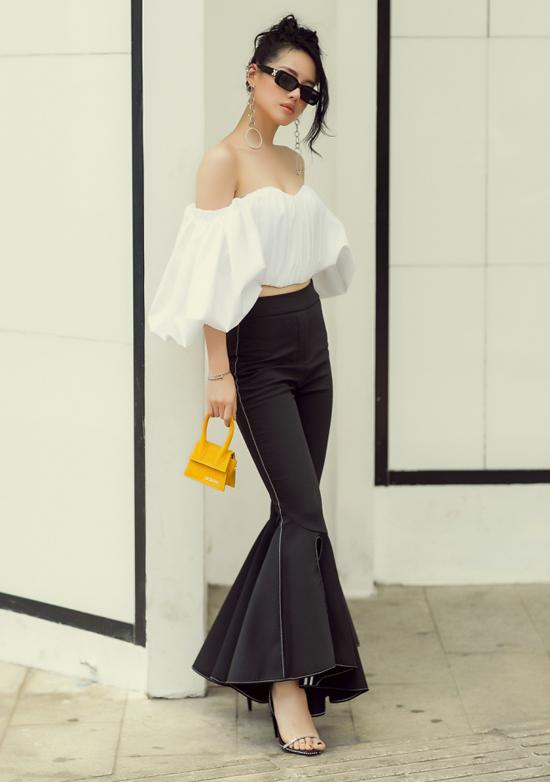 Khánh Linh thể hiện phong cách sang chảnh với áo trễ vai tay bồng, quần ống loe kiểu đuôi cá cùng các phụ kiện hoa tai to bản, túi mini nhỏ xinh.