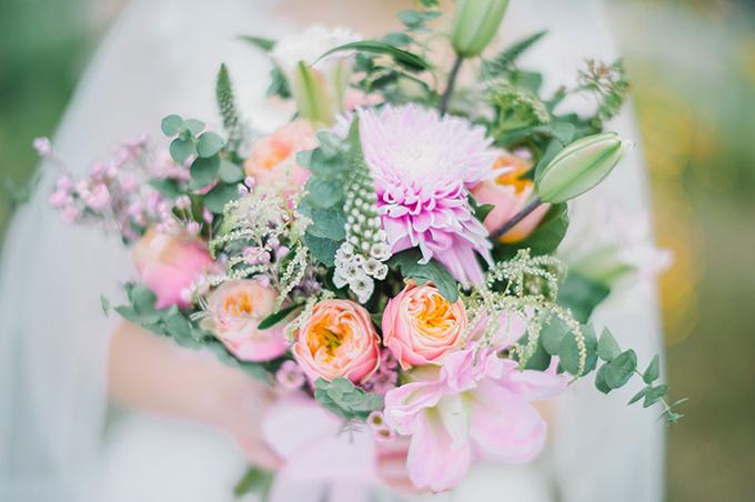 Hoa cầm tay cô dâu rực rỡ với sắc hồng cam.