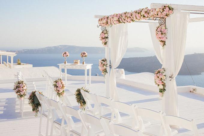 Địa điểm của đám cưới được tổ chức tại Santorini. Khách mời có thể vừa thưởng thức bữa tiệc vừa thưởng ngoạn phong cảnh lãng mạn nơi đây.