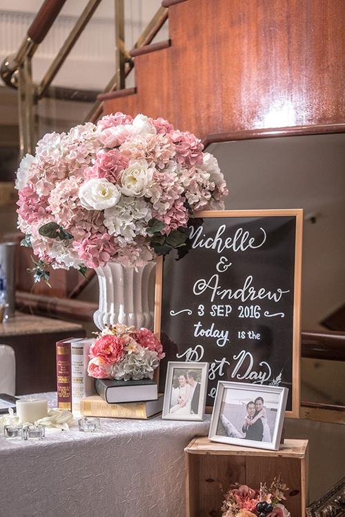 Uyên ương trang trí bàn tiệc bằng những quyển sách và bó hoa từ cẩm tú cầu, hoa hồng.