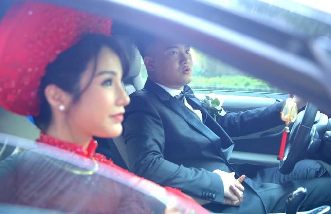 Đôi vợ chồng nắm chặt tay nhau trên xe hoa.