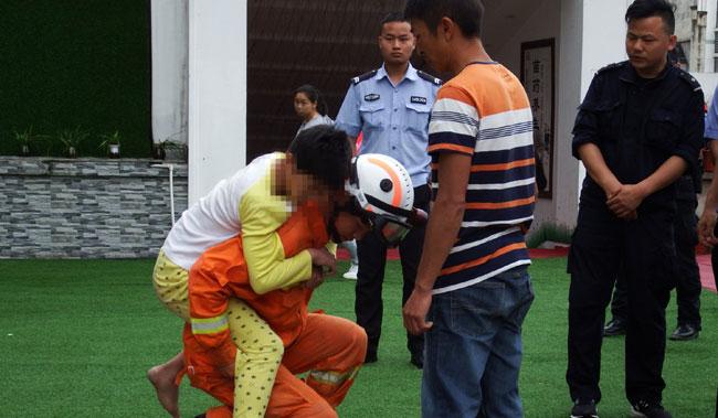 Bố cậu bé (áo kẻ ngang) túc trực bên dưới để chờ con trai được đưa xuống. Ảnh: SCMP.