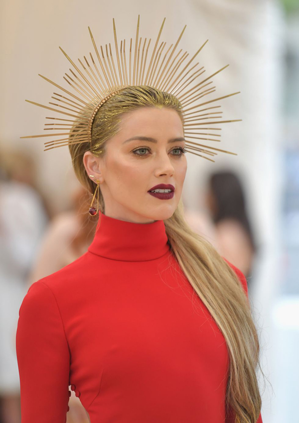 Amber Heard nổi bật trên thảm đỏ Met Gala với làn môi đỏ thẫm. Cô buộc tóc đuôi ngựa cao và đụng ý tưởng phụ kiện tóc với nhiều mỹ nhân khác.