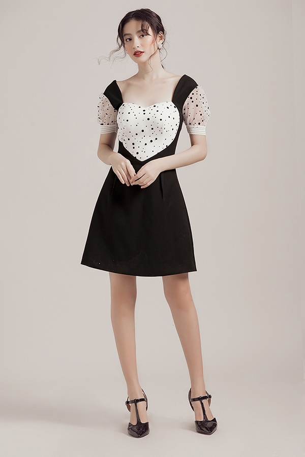 Vải in hoạ tiết chấm bi trắng đen được phối hợp nhịp nhàng và chia những mảng miếng bắt mắt trên nhiều dáng váy ngắn.