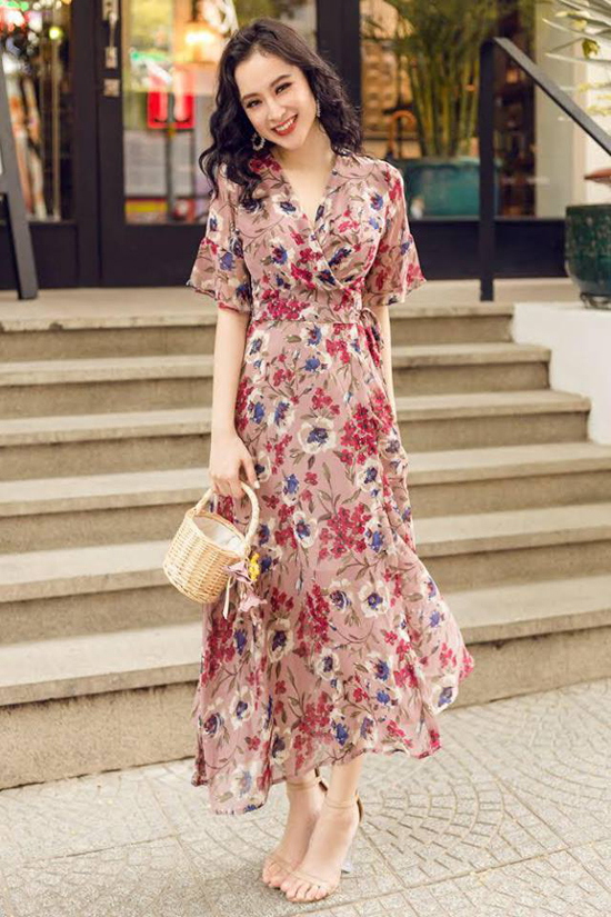 Khi diện váy hoa hợp mốt mùa hè, Angela Phương Trinh giúp mình có được tổng thể hoàn hảo hơn với cách phối sandal cao gót quai mảnh và giỏ đan xinh xắn.