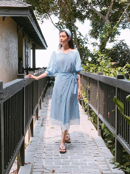 Trương Quỳnh Anh với phong cách thanh lịch, nhẹ nhàng cùng váy vạt quấn kẻ sọc. Phụ kiện cho chọn để mix cùng trang phục là khăn turban và dép trang trí hoa tạo khối 3D ấn tượng.