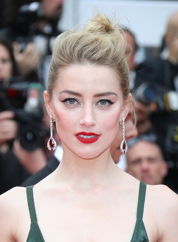 Amber Heard toả sáng với làn môi đỏ tươi. Người đẹp sử dụng hạt nhũ đính dưới mí mắt để tạo điểm nhấn.