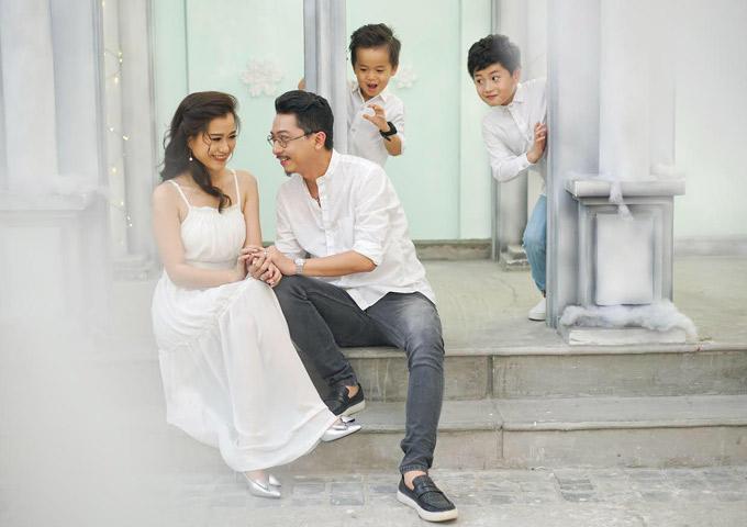 Trước mặt hai con, hai vợ chồng tình tứ nắm tay, trao nhau ánh mắt say đắm khi đi chụp ảnh gia đình.