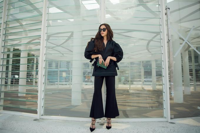 Diện một cây đen nhưng Thanh Thanh Huyền tránh được cảm giác đơn điệu khi diện đồ đơn sắc với áo tạo khối và quần loe sành điệu.
