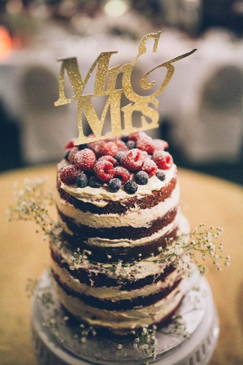 Bánh cưới được trang trí bằng quả mọng đỏ tươi.