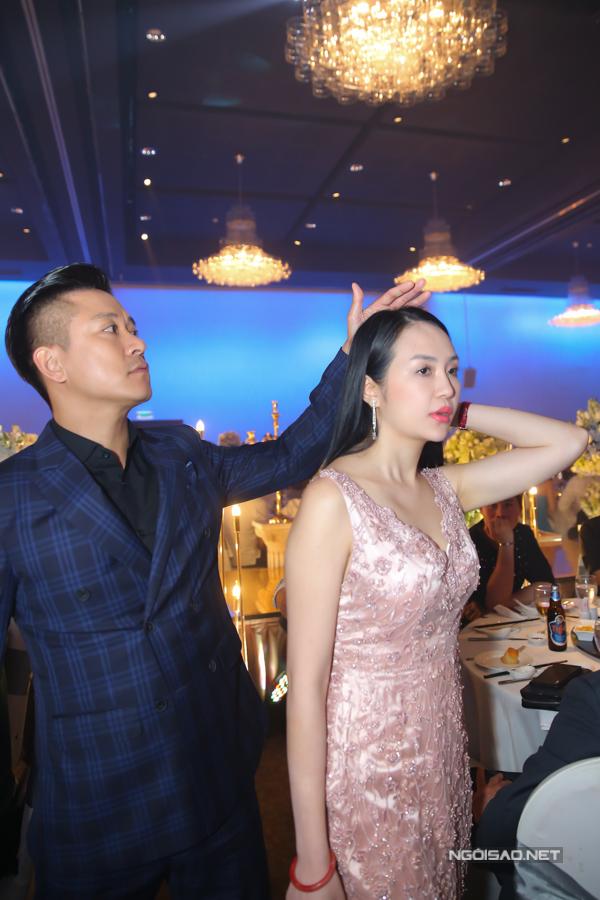 Ca sĩ người Hà Nội ân cần chỉnh sửa mái tóc cho bà xã Hương Baby khi vào dự tiệc.