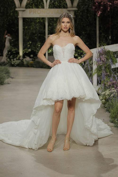 Chiếc váy cưới cúp ngực này của thương hiệu Pronovias mang vẻ lộng lẫy và bồng bềnh trong mỗi bước đi. Cộng hưởng với màu trắng tinh khiết, chất liệu ren ở nửa trên và viền váy tạo chất thơ cho thiết kế. Phom dáng trước ngắn sau dài của nửa dưới váy vẫn đang là xu hướng nở rộ trong thời gian gần đây.