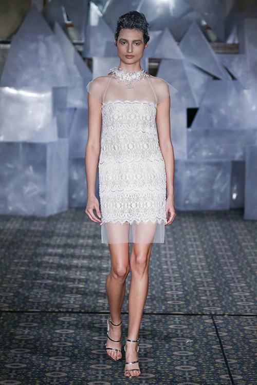 Cùng chủ đề váy cưới ngắn, nhà tạo mốt Mira Zwillinger đem đến mẫu váy dáng suông cho bộ sưu tập mùa cưới 2019. Lớp vải xuyên thấu kết hợp ren hiện đại khiến mẫu váy trông thanh thoát và tinh tế.