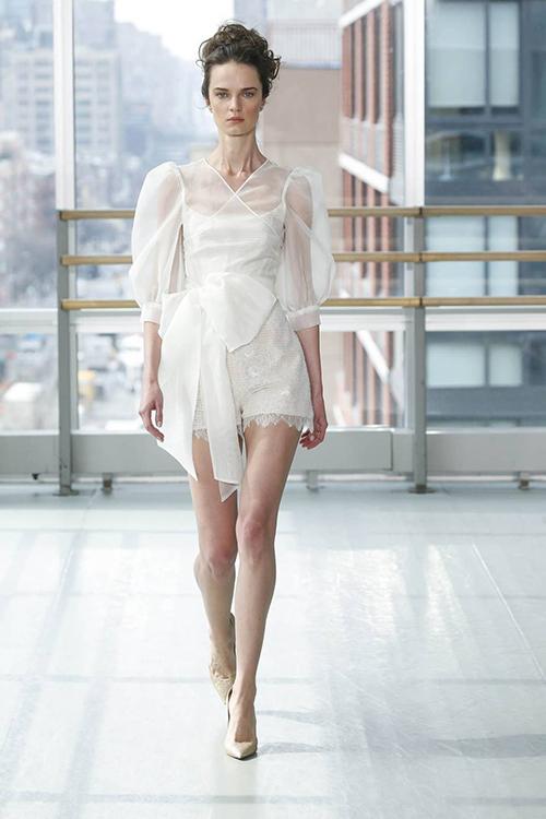 Với sự sáng tạo, chiếc váy của Gracy Accad giống một bộ jumpsuit hơn là váy cưới. Cô dâu mặc một chiếc áo hai dây màu trắng mờ cùngquần ren, khoác áo ngoài với chất liệu vải xuyên thấu và phần tay áo được xếp bồng. Một chiếc nơ to bản được thắt nút nhẹ nhàng ở eo làm điểm nhấn. Phần quần ngắn vừa đủ để phô bày khéo léo đôi chân thon thả.