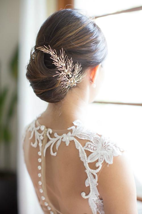 Kiểu tóc buộc thấp trang nhã được nhấn nhá bởi lược cài màu vàng đồng tinh xảo.