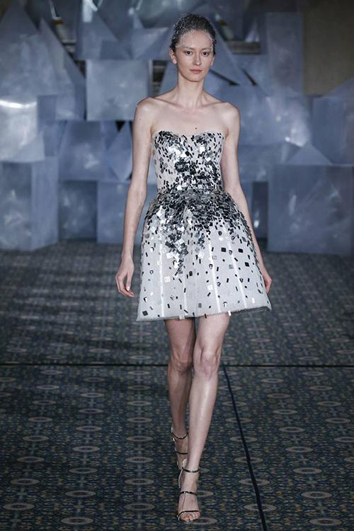 Chiếc váy được thiết kế khá đơn giản với kiểu cúp ngực điển hình và trở nên khác biệt nhờ những mảnh vải óng ánh được điểm xuyết trên thân váy. Nhờ độ dài chưa đến đầu gối, bộ váy đem đến diện mạo trẻ trung cho nàng dâu. Thiết kế váy cưới này nằm trong bộ sưu tập của thương hiệu Mira Zwillinger cho năm 2019.