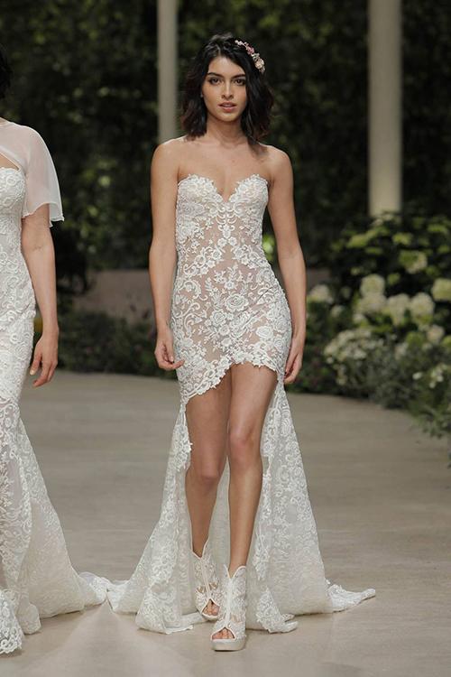 Cô dâu có thểbị thuyết phục bởi chiếc váy cưới của Pronovias. Mẫu váy cúp ngực sử dụng chất liệu ren, họa tiết hoa hồng và không thiếu những đường xẻ để lộ đôi chân thon dài. Tà váy dài quét đất khiến cô dâu trông càng thướttha và yêu kiều.